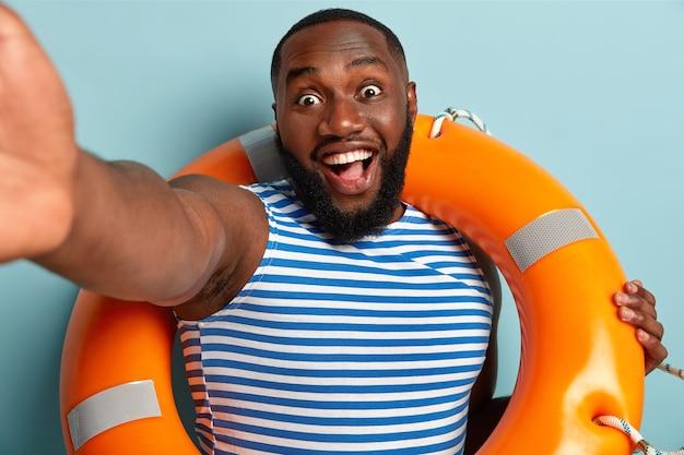 Il salvavita afroamericano emotivo e felicissimo tiene il braccio teso, posa per fare selfie, usa attrezzature salvavita, sorride ampiamente