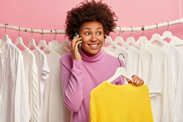 Emotional overjoyed woman makes telephone call, stands near wardobe rack full of white clothes, holds knitted winter yellow sweater, enjoys shopping day in fashion mall.
