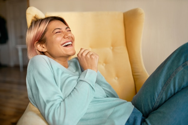 Giovane donna europea felicissima emotiva in jeans e felpa blu sdraiata sulla poltrona tenendo gli occhi chiusi