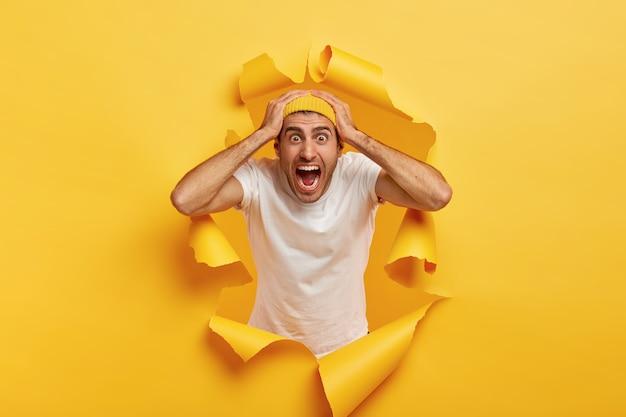 Эмоциональный паникующий молодой человек держит обе руки за голову, громко кричит, смотрит скучающими глазами, носит белую футболку