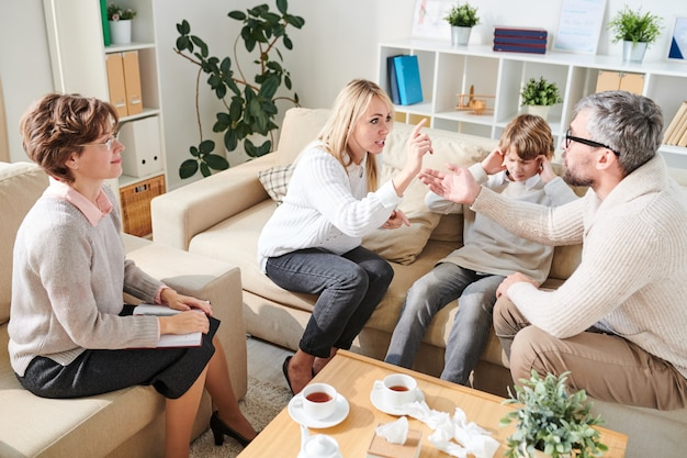 Emotional parents fighting in front of son at psychological ther