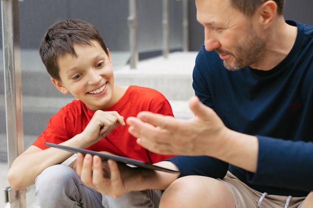 街で一緒に時間を過ごすお父さんと息子の感動的な写真。彼らはタブレットを使用し、興味を持ってコミュニケーションを取ります。父とティーンエイジャーの共同利益の概念