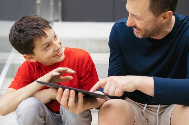 街で一緒に時間を過ごすお父さんと息子の感動的な写真。タブレットを使用して興味を持って話す