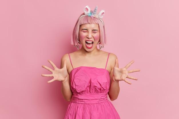 顔に化粧をしてラインストーンを付けた感情的なピンク髪のアジア人女性が手のひらを上げ、何かにイライラして怒って叫び声を上げ、スタイリッシュなドレスのユニコーンのヘッドバンドを着ている