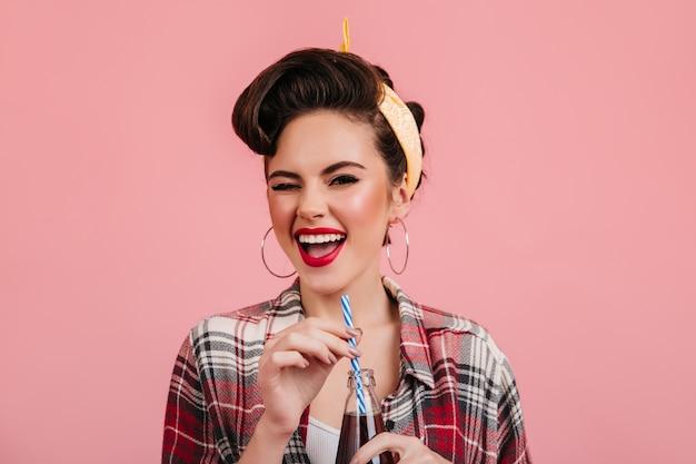 Эмоциональная девушка кинозвезды питьевой напиток. студия выстрел возбужденной молодой женщины в клетчатой рубашке, изолированной на розовом фоне.