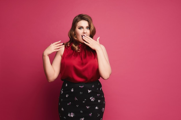 赤いブラウスとスカートで明るいメイクで感情的なプラスのサイズのモデルの女の子