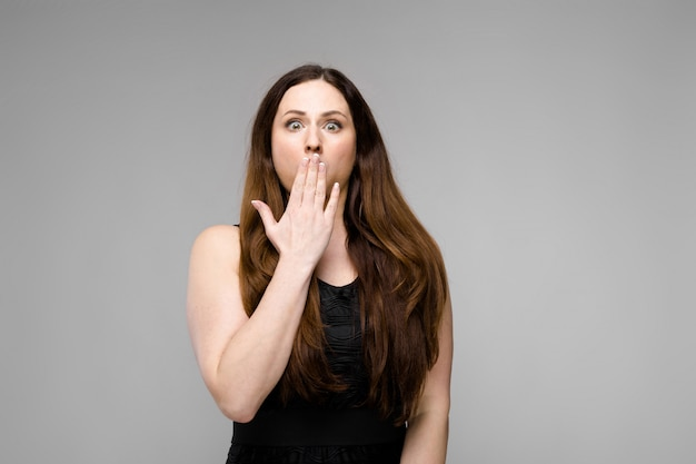 Emotional plus size model standing closing mouth with hand showing surprise astonishment on gray