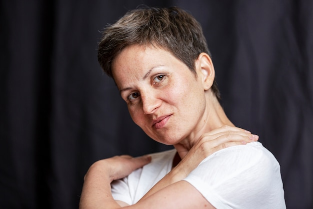 Emotional portrait of an adult woman with short hair. black background.