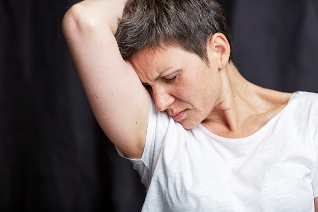 Emotional portrait of an adult woman with short hair and closed eyes. black background.