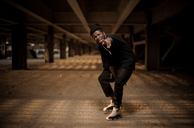 Emotional portrait of afro american man in the half squat