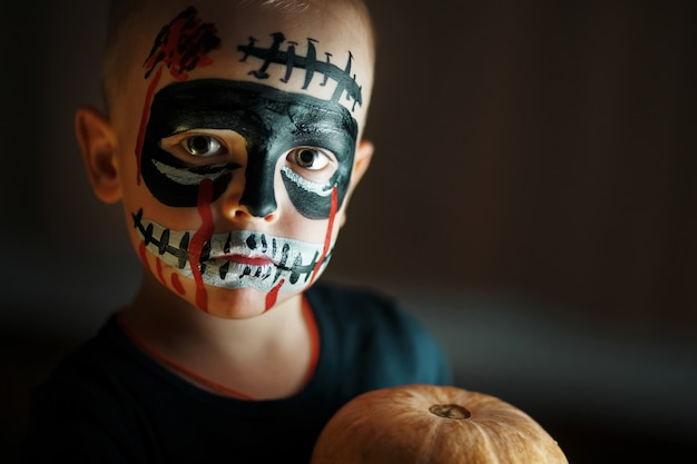 Emotional portrait of a boy with a scary zombie on his face and a pumpkin