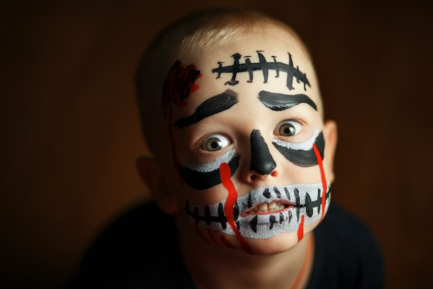Emotional portrait of a boy with a scary zombie on his face