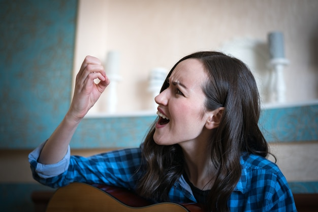Emotional portrait of brunette woman broke her nail playing an acoustic guitar.