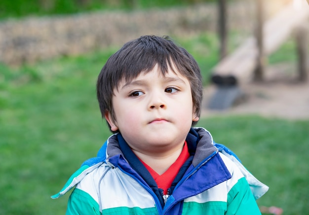 Emotional portrait of caucasian kid with thinking face, upset little boy standing alone in the park, toddler with bored face looking out deep in thought.