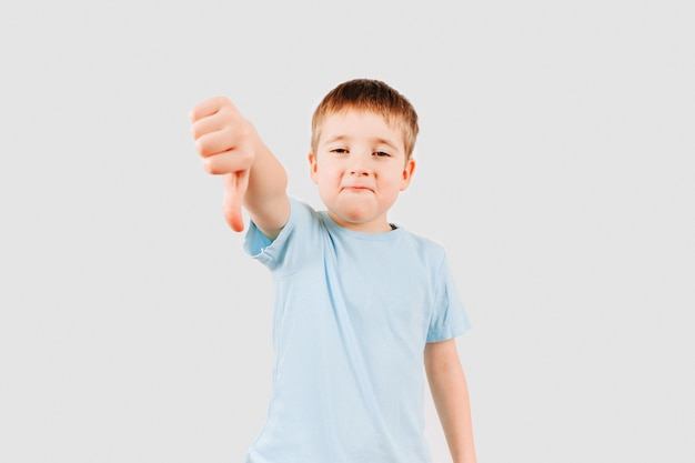Emotional portrait of kid boy giving thumbs down hand gesture