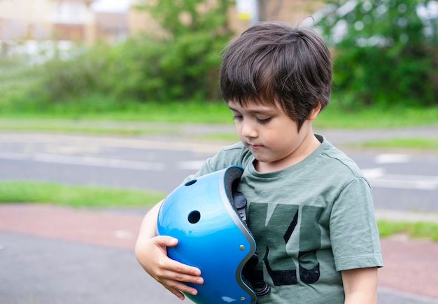Emotional portrait of kid boy with upset face holding safety helmet standing next to the road, lonely child looking down with sad face standing alone on pathway