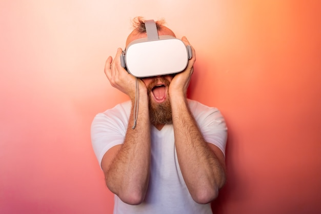 Emotional portrait of a man with a beard wearing virtual reality glasses in the studio on a pink orange background