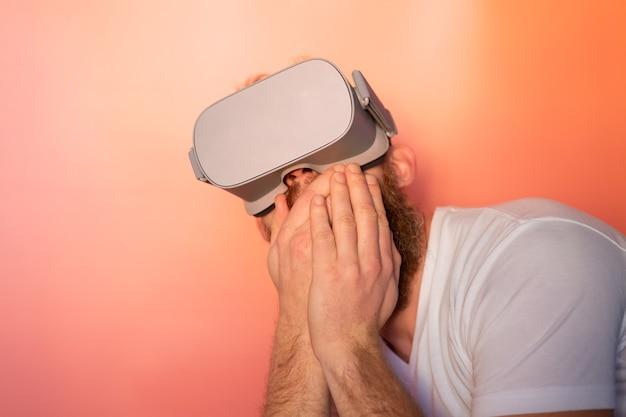 Ritratto emotivo di un uomo con la barba che indossa occhiali per realtà virtuale in studio su uno sfondo rosa arancio