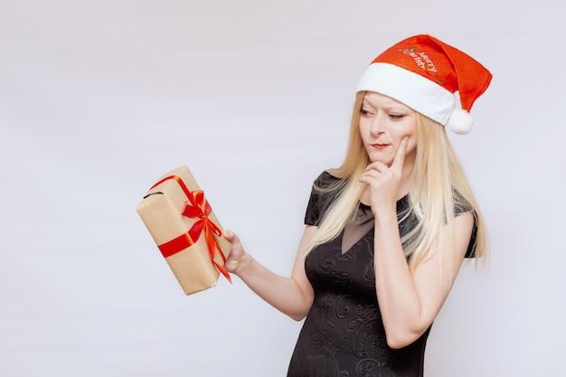 Эмоциональный портрет красивой девушки с подарочной коробкой в руках в новогодней шапке