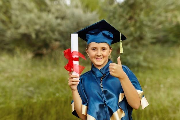 졸업장을 들고 야외에서 파란색 졸업 가운을 입고 모자를 쓴 행복한 대학원생의 감정적 초상화. 승리를 축하하는 운이 좋은 쾌활한 여학생.