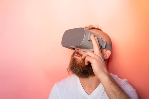 Эмоциональный портрет мужчины с бородой в очках виртуальной реальности в студии на розово-оранжевом фоне