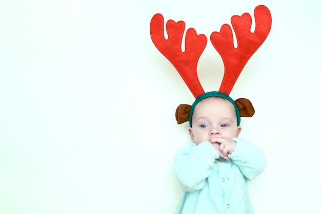 クリスマスのトナカイの角で生まれたばかりの赤ちゃんの感情的な肖像画