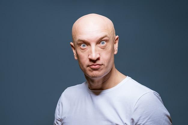 회색 배경 클로즈업에 흰색 티셔츠를 입은 성인 대머리 남자의 감정적 초상화