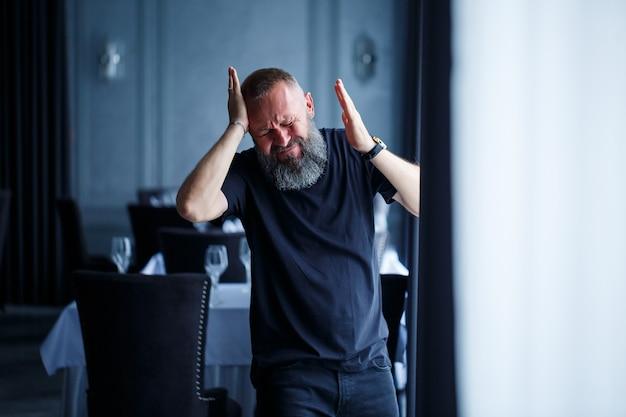 Эмоциональный портрет взрослого седого мужчины с бородой в черной футболке