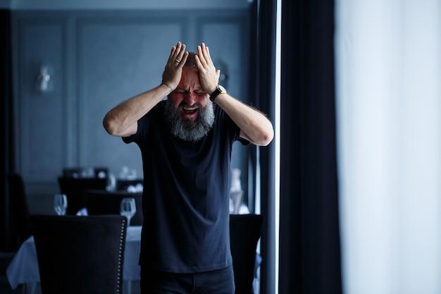 黒のtシャツにひげを生やした大人の白髪の男の感情的な肖像画