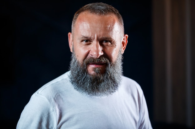 Эмоциональный портрет взрослого седого мужчины с бородой в белой футболке