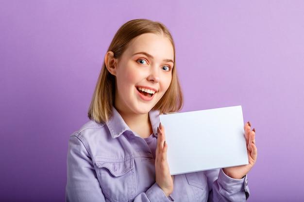행복한 젊은 여성의 감정적 초상화는 빈 모형 흰색 카드를 보여줍니다. 복사 공간으로 성공을 축하하는 행복한 미소 짓는 여성은 보라색 배경 위에 텍스트를 위한 빈 빈 보드를 조롱합니다.