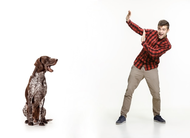 Эмоциональный портрет человека и его собаки, концепция дружбы и заботы о человеке и животном. немецкий короткошерстный пойнтер - щенок курцхаара, изолированные на белом фоне студии