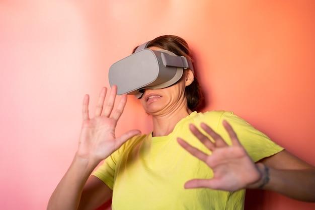 ピンクオレンジ色の背景にスタジオで仮想現実メガネの女性の感情的な肖像画