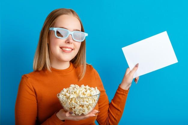 영화 안경에 젊은 여자의 감정적 초상화입니다. 푸른 색 배경 위에 격리된 모의 복사 공간을 위해 팝콘과 엠티 흰색 블랑 카드를 들고 안경을 쓰고 웃고 있는 10대 소녀 영화 뷰어.