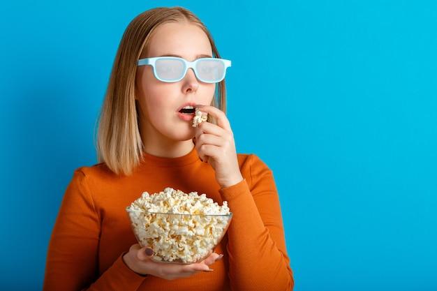 3d 영화를 보는 영화관 안경을 쓴 젊은 여성의 감정적 초상화. 안경을 쓴 열렬한 10대 소녀 영화 뷰어는 파란색 배경 위에 격리된 복사 공간이 있는 팝콘을 먹습니다.