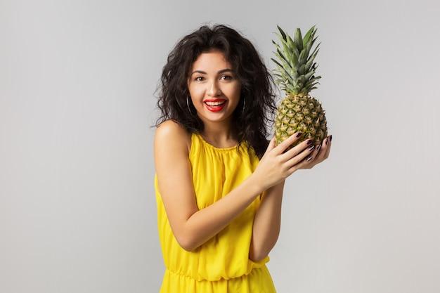 Ritratto emotivo di giovane donna bruna esotica in abito giallo, che tiene ananas, espressione faccia buffa, emozione positiva, isolato, frutta tropicale, dieta, felice, sorridente, stile di vita sano