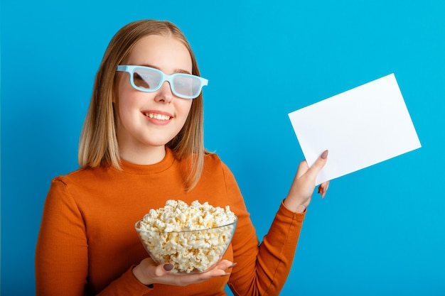 Emotional portrait of young woman in cinema glasses. smiling teenager girl movie viewer in glasses holding popcorn and emty white blanc card for mock up copy space isolated over blue color background.