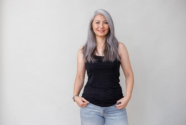 灰色の壁に青白い長い髪のアジアの成熟した女性の感情的な肖像画