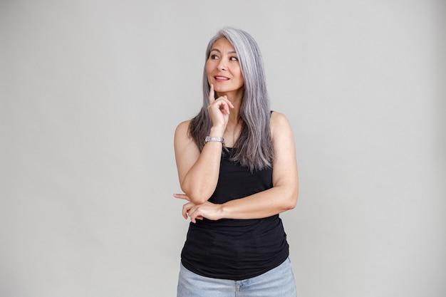 회색 벽에 창백한 긴 머리 아시아 성숙한 여자의 감정적 초상화