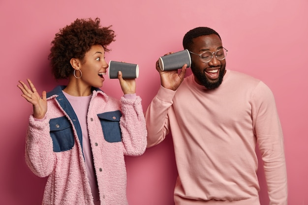 Emotional positive african american woman and man have fun with paper coffee cups, shout and listen attentively, have joyful expressions