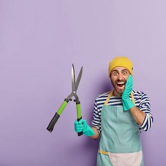 Giardiniere maschio emotivo positivo tiene cesoie da potatura affilate, pronte per il taglio di cespugli o alberi, indossa guanti di gomma, aproon blu