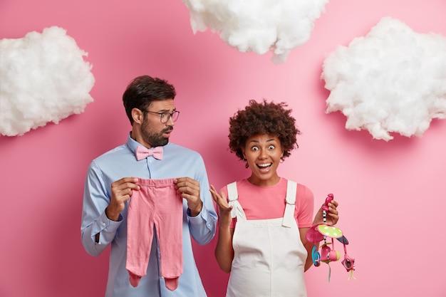 Эмоциональная беременная женщина громко кричит, реагирует на что-то, что держит мобильную игрушку, позирует рядом с мужем