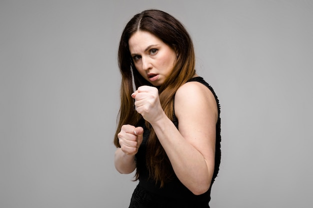Emotional pretty confident serious plus size model standing in studio boxing on gray