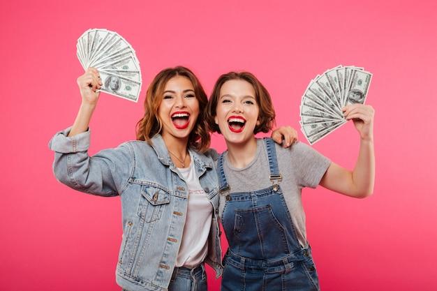 Emotional pretty two women friends holding money