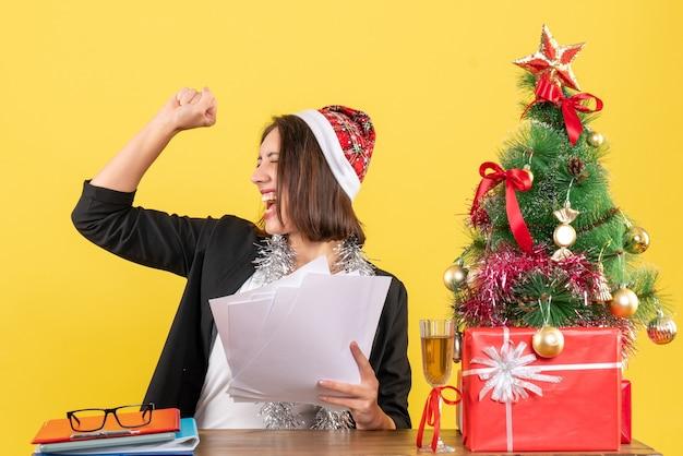 Emotiva donna d'affari orgogliosa in vestito con cappello di babbo natale e decorazioni di capodanno che tiene documenti e seduto a un tavolo con un albero di natale su di esso in ufficio