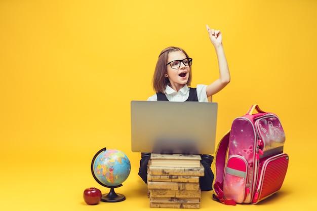 감정적 인 학생은 노트북으로 책 더미 뒤에 앉아 집게 손가락 어린이 교육으로 손을 올립니다