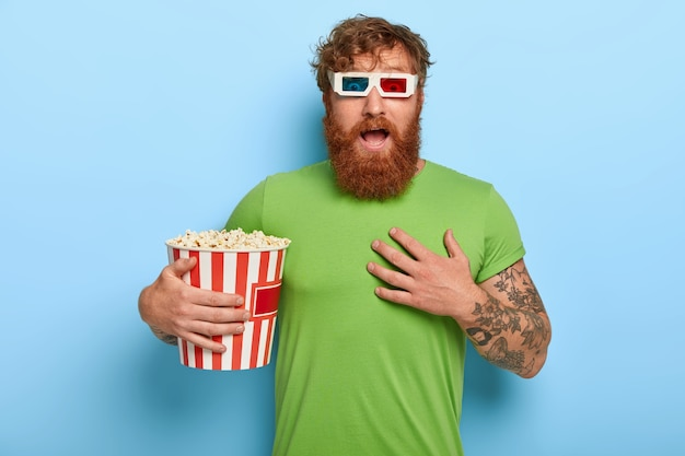 感情的な赤毛の男は大きな恐怖で見え、映画館で一人でホラー映画を見て、息を切らしました