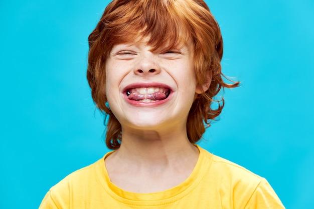 혀 클로즈업 노란색 티셔츠 파란색 벽을 물고 감정적 인 빨간 머리 소년