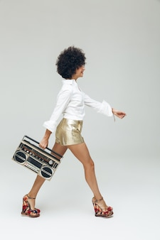 Emotional retro woman dressed in shirt holding boombox.
