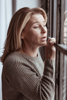 Emotional and sad. green-eyed mature woman feeling emotional and sad standing near the window